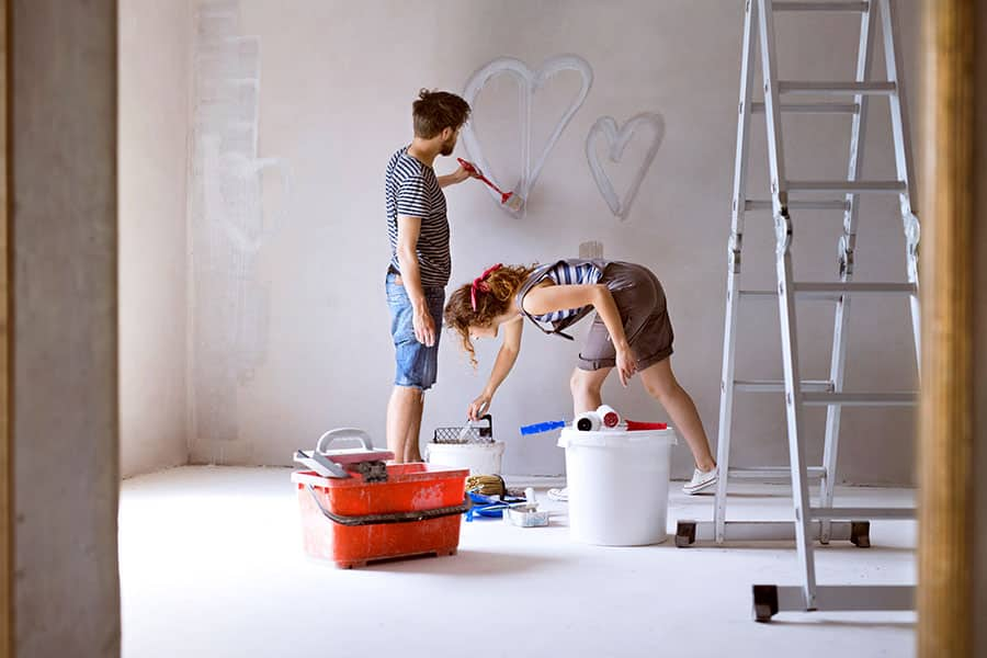 Couple painting hearts on the wall in their house