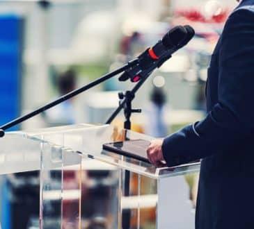 Speaker Standing In Front Of Microphones
