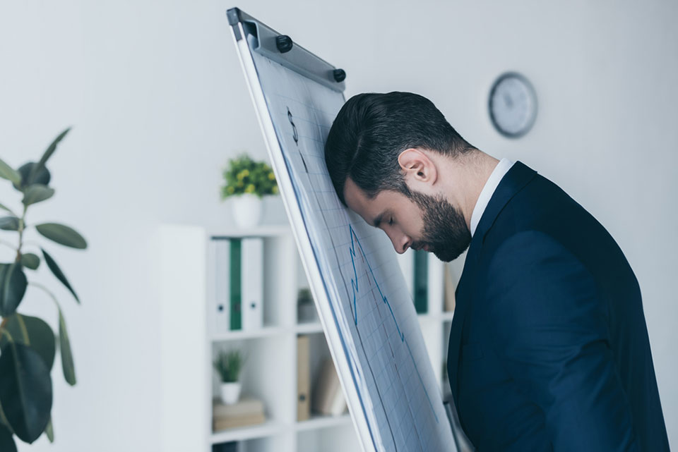 Depressed businessman standing with closed eyes and leaning at flipchart with forehead